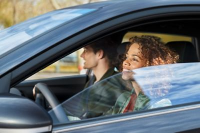 A woman and man sit in an all-new Hyundai i20 with the driver's side window half down, outside view