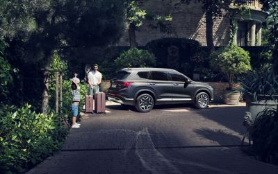 The new Hyundai SANTA FE Hybrid 7 seat SUV from the front, parked in front of a house.